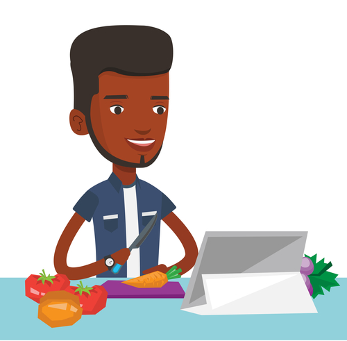 Man cutting healthy vegetables for salad. Man following recipe for vegetable salad on digital tablet. Man cooking healthy vegetable salad.